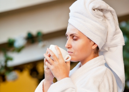 Young woman after bath enjoyed with morning coffee aroma photo