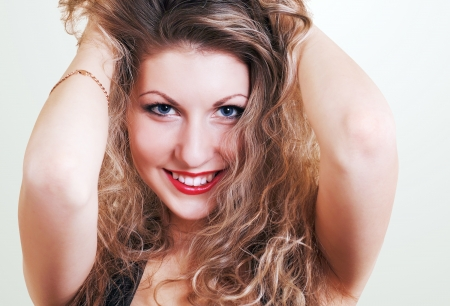 Beautiful smiling girl portrait with blonde long curly hair photo