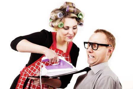 Careful houswife ironing the necktie for shocked husband photo