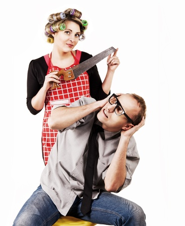 submissive: Concept family scene. Defaulter husband and wife with hacksaw Stock Photo