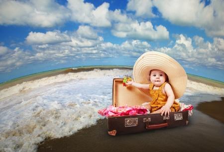 ropa de verano: Viajando por el mundo del beb� que se sienta en la maleta en la costa del mar