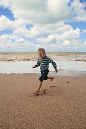 shoeless: Shoeless happy little boy running at the sea coast