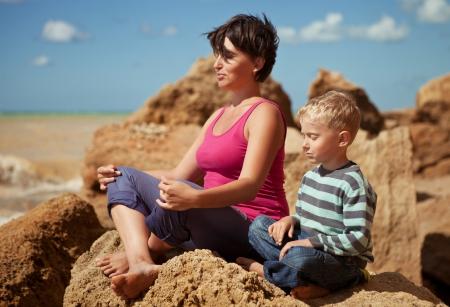 persona respirando: Madre e hijo en la relajación sentada plantean en el mar costa