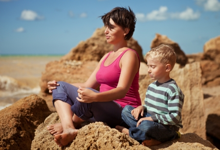 kids exercise: Mother and son in sitting relaxation pose at sea coast
