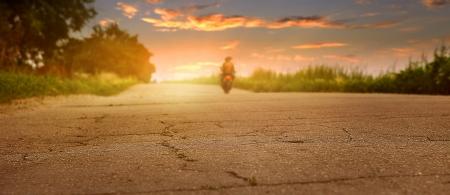 motociclista: Puesta de sol con la silueta desserted carretera del motorista