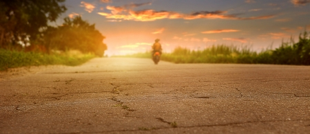motorcyclist: Sunset desserted highway with biker silhouette