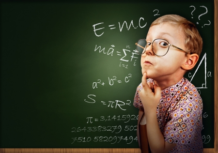 science lesson: Funny portrait clever pupil boy on school board background