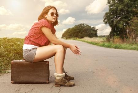 mujer hippie: Chica joven en la carretera vac�a esperando sin coches