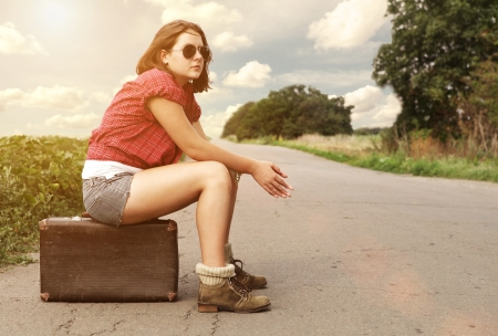 Young girl on the empty highway waiting for free car photo