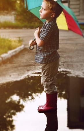 rainwear: Little boy under bright umbrella after summer rain