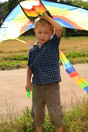 Boy with bright kite in hand in sunny day photo
