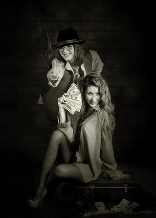 Two beauty swindler girls with case of money. Retro style photo