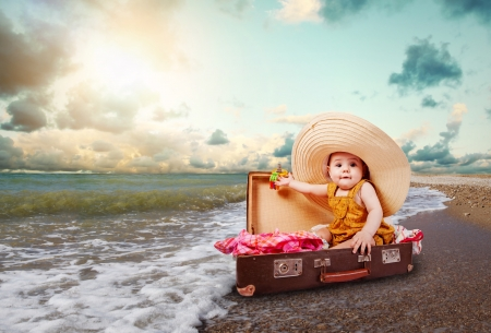 Funny baby girl traveler sitting in retro suitcase at the sea coast photo
