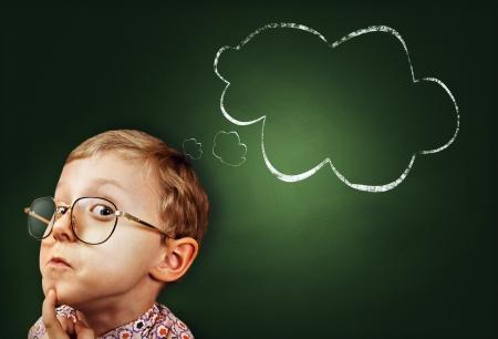 egghead: Riflessivo ragazzo portait divertente con Idea astratta nuvole sulla lavagna