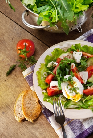 Light caloried salad with fresh rucola, tomatoes and poached egg