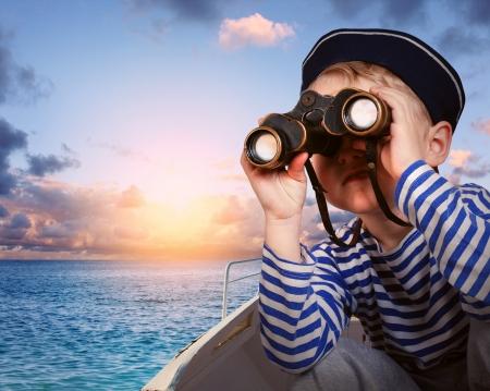 marinero: El ni�o peque�o con uniforme de marinero con binoculares en el bote Foto de archivo