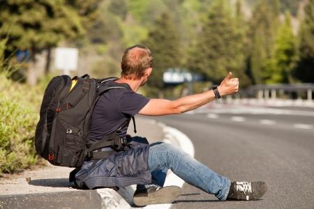 자동차 편승 여행자는 산 고속도로의 길가에 앉아