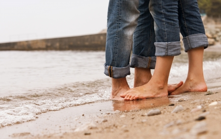 barefoot people: Closeup image barefoot couple legs on the sea coast Stock Photo
