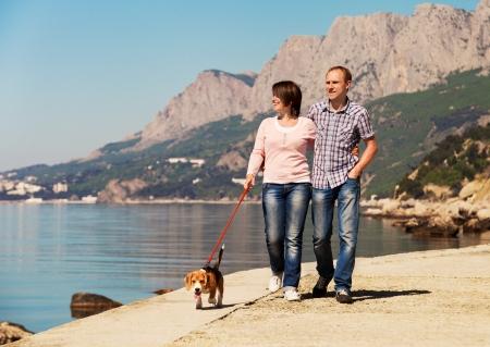 dog days: Feliz pareja caminando con cachorro beagle en la costa