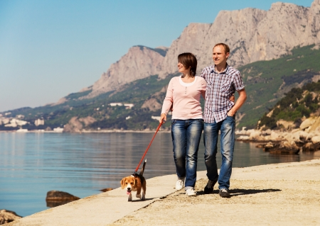 Happy couple walking with beagle puppy at the seacoast