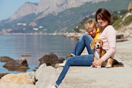 beagle puppy: Happy mother and son sitting on the quay with beagle puppy