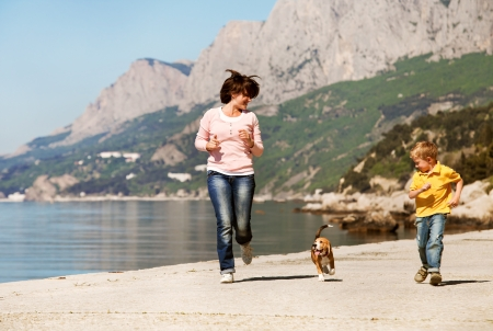 Mother and son playing with beagle puppy at the sea coast photo