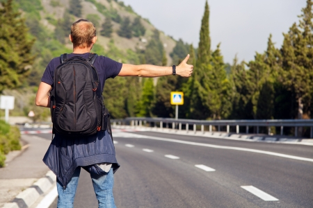 hitchhiking: Hitchhiking travel man at the route Stock Photo