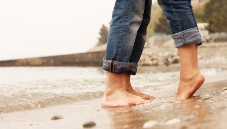 Closeup image barefoot couple legs at the beach photo