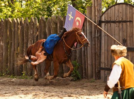 the cossacks: Zaporizhia, Ucrania - 18 de mayo 2013: Trucos en galope de caballos de los cosacos Horse espect?culo de teatro en la isla Khortytsia. Cosacos Horse teatro en Zaporizhia, 18 de mayo de 2013. Editorial