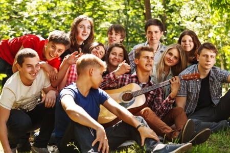 Group of young people singing by guitarin summer park photo