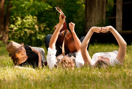 Happy teenage friends relax with guitar music on the green medow photo
