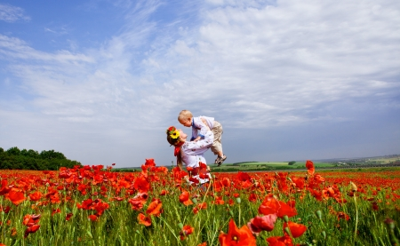 children holding hands: Happy ukrainian mother with son on the poppies field