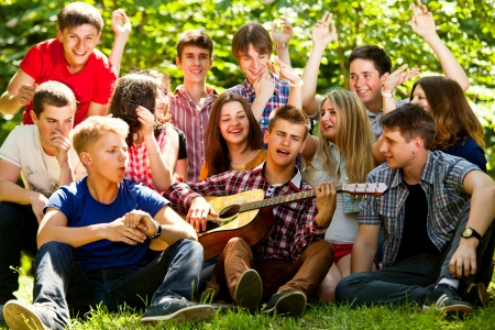 Ggroup of young people singing in unison by guitar Imagens
