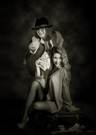 swindler: Two beauty swindler girls with case of money. Retro style