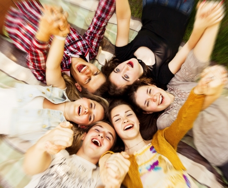 genießen: Kreis der glücklichen Teenager-Freunde auf dem Rasen lag mit hans up