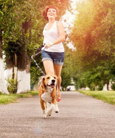 그녀의 비글 강아지와 함께 조깅 행복 한 젊은 여자 스톡 콘텐츠
