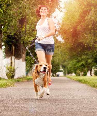 walking in park: Happy young woman jogging with her beagle dog