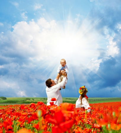 Happy family with little son in traditional ukrainian dress on th epoppies field photo