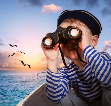 Sailor boy looks at horizon from binoculars
