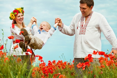 Parents playing with little son on the poppies field photo
