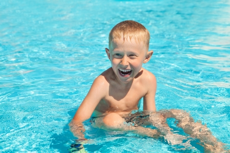 Happy smiling little boy sitting into the pool photo