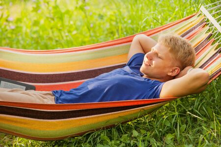 Smiling young man have a relax time in hammock photo
