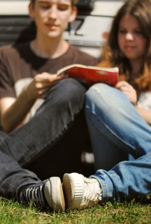 Closeup image of young couple sitting on grass near the car and read guidebook