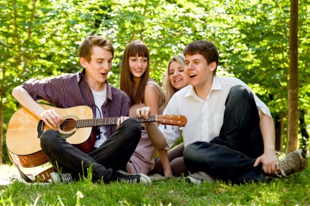 Four happy smiling teenage friends singing by guitar photo