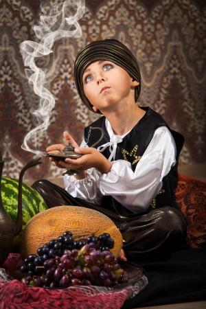 genio de la lampara: Ni�o peque�o en traje oriental alcance sorprendi� con l�mpara m�gica Foto de archivo