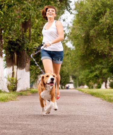 dog park: Happy young woman jogging with her beagle dog