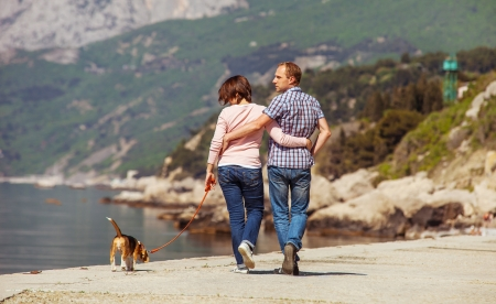 dog days: Amor pareja caminando con cachorro beagle en la costa del mar