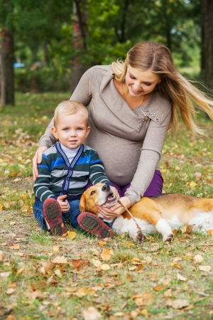 Carefree pregnant woman with little son and pet walk in autumn park photo