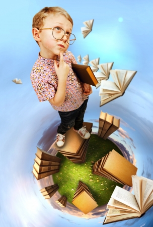 Cute little boy in glasses standing on abstract book planet photo