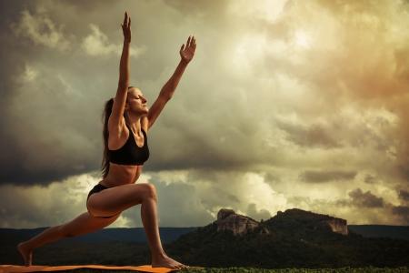Young woman makes sun salutation yoga exercise